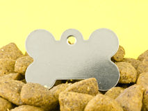Blank dog tag. In Kibble on a Yellow Background Stock Photo