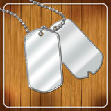 Blank dog tags on a wooden background Royalty Free Stock Images