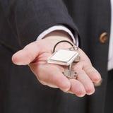 Blank door keychain on businessman's palm. Close up stock photos