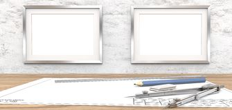 Blank drawings and Frames for copy space. Blank blueprint on table. 2 Blank Picture Frames on white concrete Wall. Copy Space. Ruler, Pencil and Divider of Royalty Free Stock Photo