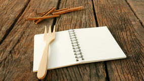 The blank earth tone note book on old dark brown wooden planks Royalty Free Stock Photos