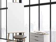 Blank easel in interior. Blank easel, stool and counter with paint palette in interior. Framed window with New York city view in the background. Mock up, 3D Stock Photos