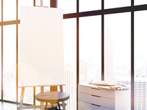 Blank easel toning. Blank easel, stool and counter with paint palette in interior. Framed window with New York city view in the background. Toned image. Mock up Royalty Free Stock Photography