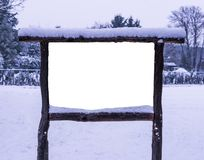 Blank and empty advertisement board covered in white snow, isolated and cut out, snowy forest background stock photography