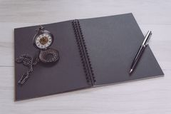 Blank empty black page note book opening with pen and vintage pocket watch on gray wooden table using as time, journal thinking, royalty free stock image