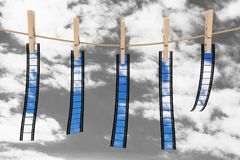 Blank and Empty Films Hanging on Rope by Wooden Clothespins. 3d. Blank and Empty Films Hanging on Rope by Wooden Clothespins on a blue sky background. 3d Stock Photography
