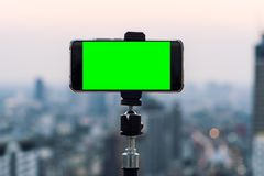 Blank empty green screen mobile smartphone taking a photo or video live on a tripod with blurry city background in social royalty free stock images