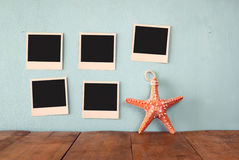 Blank empty instant photos hang over wooden textured background next to decorative starfish. retro filtered image Royalty Free Stock Photo