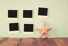 Blank empty instant photos hang over wooden textured background next to decorative starfish. retro filtered image Stock Image
