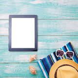 Blank empty tablet computer on beach. Trendy summer accessories on wooden background pool. Flip-flops on beach. Tropical flower or Stock Images