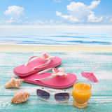 Blank empty tablet computer on beach. Trendy summer accessories on wooden background pool. Flip-flops on beach. Tropical flower or Stock Image