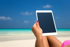 Blank empty tablet computer in the hands of women on the beach Stock Image