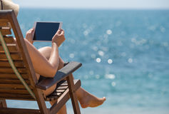 Blank empty tablet computer in the hands of women on the beach stock images