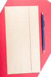 Blank envelop and pen on red backdrop Stock Images