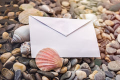Blank envelope on the beach decorated with sea shell. Blank envelope on the sea shoreline decorated with shell Royalty Free Stock Image