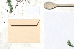 Blank envelope and business card near wooden spoon and flavorings. 3D rendering. stock image