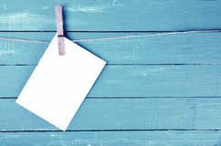 Blank envelope hanging on rope on wooden clothespin. Blue background Stock Photos