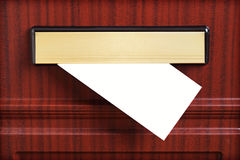 Blank envelope through mail slot Stock Images