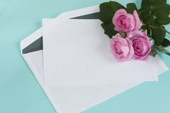 Blank envelope and pink roses flowers bouquet. stock photography