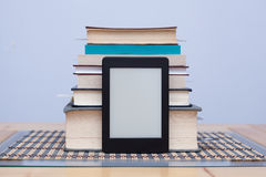 Blank eReader in front of a tower of books with bookmarks Stock Photography