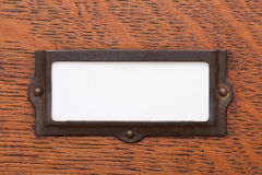 Blank File Drawer Label. Close up of a blank, white label in an old brass label holder on an oak filing cabinet drawer Stock Photography