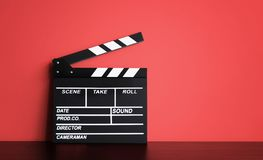 Blank Film clapper board or movie clapper cinema board , Slate film on black wooden with red wall background .cinema concept royalty free stock photography