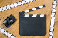 Blank film slate, vintage camera and film Royalty Free Stock Photo
