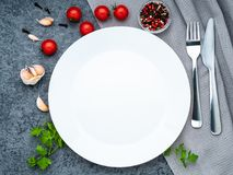 Blank flat white plate, fork on dark gray stone concrete table, top view. Mock up, copy space royalty free stock photo