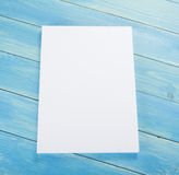 Blank flyer poster on wooden background to replace your design. Royalty Free Stock Images