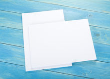Blank flyer poster on wooden background to replace your design. Royalty Free Stock Photo