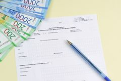 The blank form of the tax document in the Russian language `Declaration on the tax to incomes of physical persons form 3-NDFL`. Pen and new money to pay the stock photo