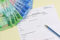 The blank form of the tax document in the Russian language `Declaration on the tax to incomes of physical persons form 3-NDFL`. Pen and new ruble banknotes for royalty free stock photo