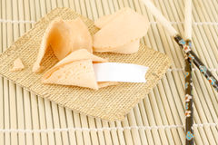 Blank fortune cookies. And chopsticks on a bamboo background Royalty Free Stock Image