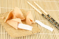 Blank fortune cookies. And chopsticks on a bamboo background Stock Photos