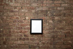 Blank Frame on Brick Wall. An empty black frame hanging on a brick wall Stock Image