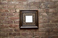 Blank Frame on Brick Wall. An empty ornamental frame hanging on a brick wall Royalty Free Stock Photography