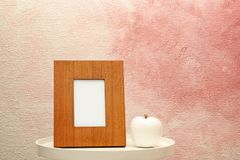 Blank frame and decorative apple figure on table near color wall. Royalty Free Stock Photos
