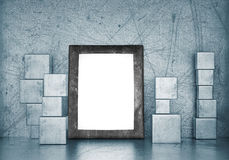 Blank frame in empty room with metal cubes Royalty Free Stock Photo