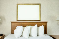 Blank Frame Over Bed. An empty frame hangs on the wall over a bed Royalty Free Stock Photos
