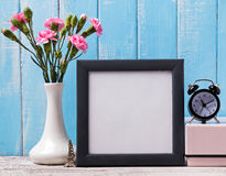 Blank frame, pink flowers, alarm clock and souvenir Eiffel tower Stock Images