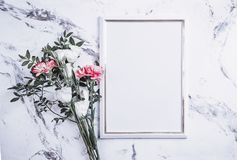 Blank frame and pink flowers over marble table Royalty Free Stock Image