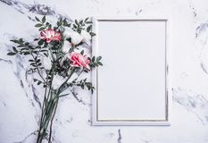 Blank frame and pink flowers over marble table Royalty Free Stock Photo