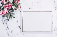 Blank frame and pink flowers over marble table Stock Photo