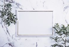 Blank frame and pink flowers over marble table Royalty Free Stock Photography