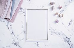 Blank frame and sewing items over marble table Royalty Free Stock Photos