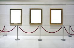 Blank framed canvas in an exhibition. 3 blank framed canvas on a wall surrounded by a rope barrier stock images