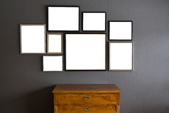 Blank frames in different sizes on a gray wall. With a wood dresser in the front Royalty Free Stock Photos