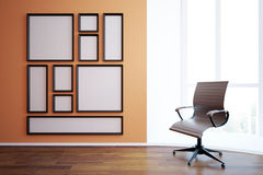 Blank frames and swivel chair. Front view of blank picture frames in interior with empty swivel chair, wooden floor and window with city view and daylight. Mock Stock Images