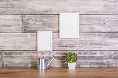 Blank frames on wooden backgrounf. Blank picture frames, plant and watering-can on wooden background. Mock up stock photo