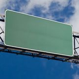 Blank freeway sign in blue cloudy sky stock images